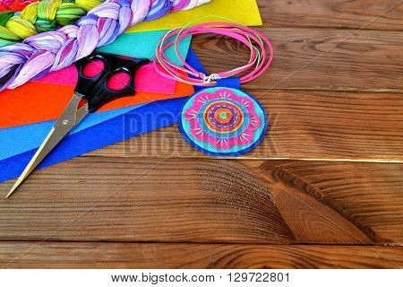 Colorful felt pendant  jewelry. Scissors, sheets of felt on a wooden background with copy space for text