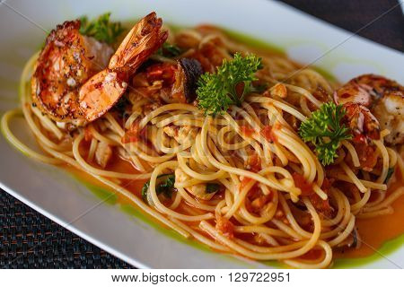 Spaghetti with shrimp on a white plate