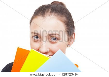 Happy smiling student girl looking trough colorful notebooks, isolated on white background