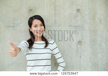 Woman showing thumb up against concrete background