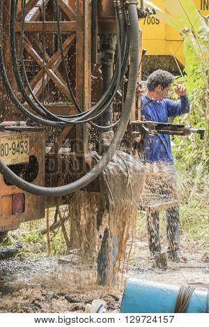NAKHON SI THAMMARAT THAILAND - DECEMBER 7: Man working a drilling rig to a water well for crop irrigation on December 7 2015 in Nakhon Si Thammarat Thailand.