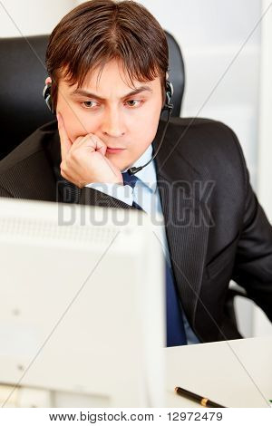 Serious businessman with headset sitting at office desk and looking at computer monitor