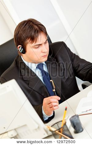 Serious business man with headset sitting at office desk and checking timetable in diary