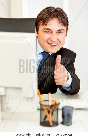 Smiling businessman looking from computer monitor and showing thumbs up gesture