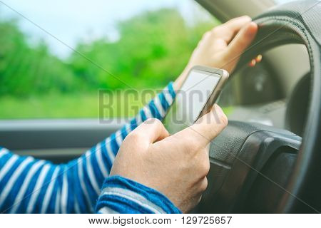 Female driving car and texting sms message on smartphone using mobile phone in traffic selective focus