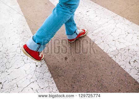 Young teenage person wearing blue jeans and red sneakers walking over pedestrian zebra crosswalk selective focus