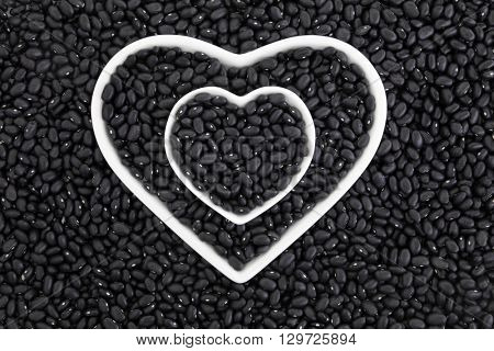 Black turtle bean super health food in porcelain heart dishes forming an abstract background.