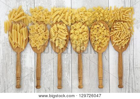 Dried pasta italian food in oak wood spoons and loose over distressed white wood background. Penne, farfalle, fusilli, messicani, ditali rigati and macaroni varieties from left to right.
