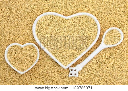 Millet grain super food in heart shaped bowls and porcelain spoon forming an abstract background.
