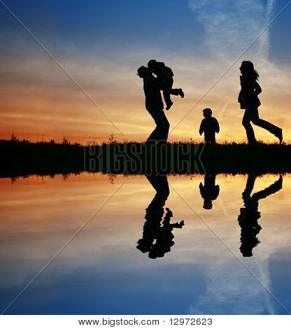 silhouette family of four and water