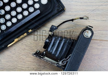 Overhead image of an old fashioned vintage typewriter with bellows camera
