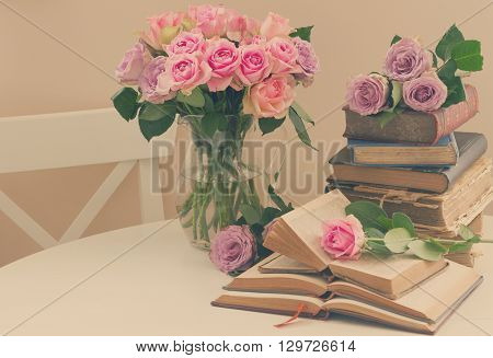 Pile of old books with bouqet of  rose flowers, retro toned