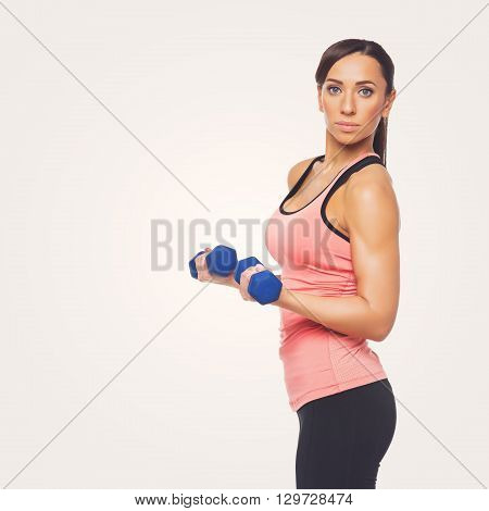 Beautiful sporty woman in sportwear making exercise with blue dumbbells. Isolated over white background. C