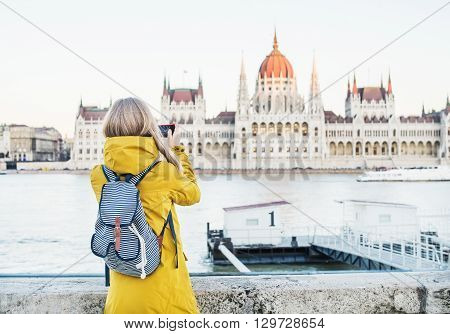 Young blondy woman tourist making photos of Parliament historic building from Danube side with her phone in Budapest, Hungary, on a spring clear day