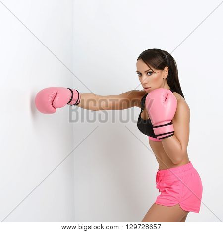 Beautiful sporty fit young woman in sportwear and pink boxing gloves. Over white background. Square composition. Copy space.