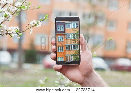 Hand with smartphone taken pictures of multi-storey building.