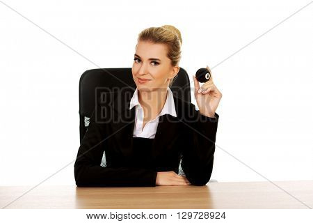 Businesswoman holding eight billiard ball by a desk