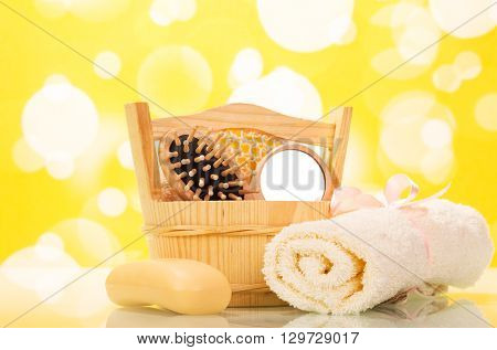 Soap, towel and a hairbrush in the bathroom on a yellow background