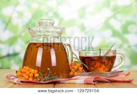 drink of sea buckthorn on a background of green leaves