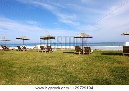The ambrellas blue sea and sky on the cretan beach in Greece.