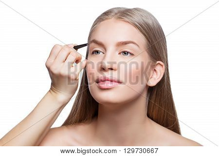 Beautician correcting eyebrows form on beautiful woman face. Beauty shot. Close-up.