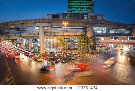 Bangkok Thailand - May 10 2016: Movement of cars in a traffic in Bangkok (called Siam) after sunset. There was a moving skytrain on the rail above the road.
