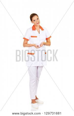 Young female doctor or nurse holding pink breast cancer awareness ribbon