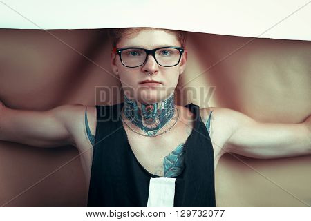 A Young Blond Man In Glasses With A Pierced Nose And A Tattoo Throwing On His Head A White Cloth.guy