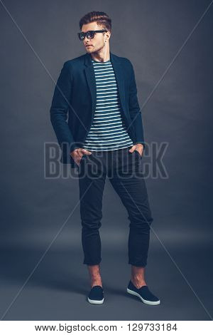 He is so stylish. Full length of confident young handsome man keeping hands in pockets and looking away while standing against grey background