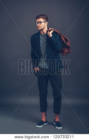 Confident in his style. Full length of confident young handsome man in glasses holding bag and looking away while standing against grey background