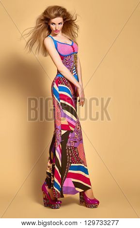 Fashion blonde woman in colorful luxury summer dress, glamor shoes with volume hairstyle, make up. Beauty sexy model in stylish bright clothes. Expressive playful vivid girl. Unusual creative lady.