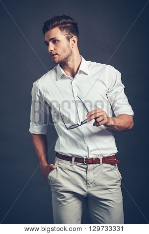 Confident in his style. Confident young handsome man looking away while standing against grey background
