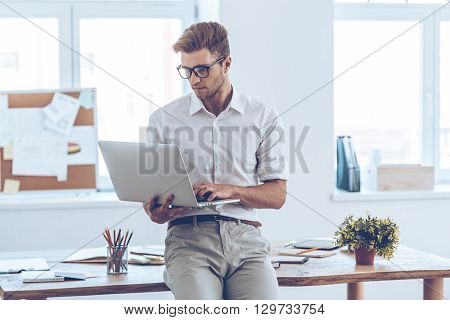 Managing everything with one click. Handsome young man in glasses using his laptop while leaning to the table in office
