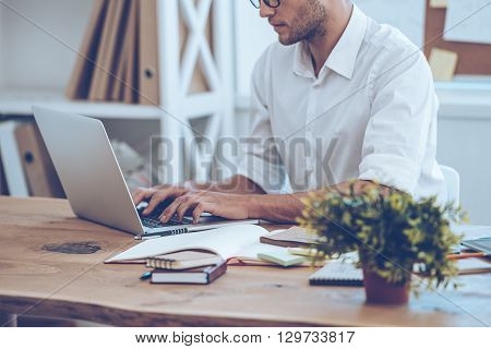 Manager at work. Side view part of young man in glasses working with laptop while sitting at his working place