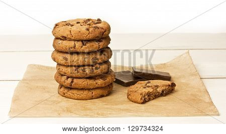 A stack of chocolate chips cookies and a half of one with a couple of pieces of dark chocolate on a sheet of baking paper with copyspace