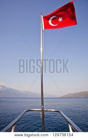 Turkish flag on a ship mast with sea background.