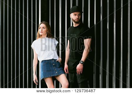 Stylish and fashionable couple posing on a background of a metal fence. Young man with a beard wearing a stylish black clothes. Beautiful fashionable girl in a denim skirt. Fashionable couple