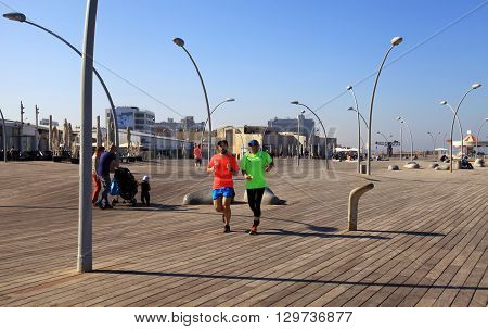 TEL AVIV, ISRAEL - APRIL 1, 2016: Men runs on new promenade in Tel Aviv port Israel.