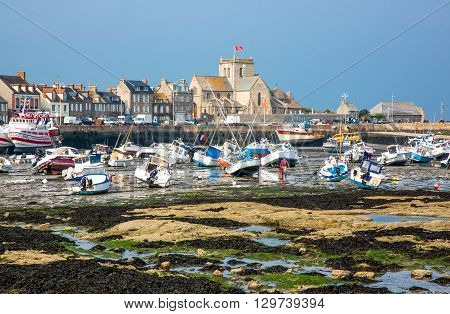 Barfleur France - May 21 2012: Normandy view of the harbor and boats at low tide near the village.