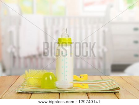 Small bottle with a nipple and milk, brush for washing dishes in the background