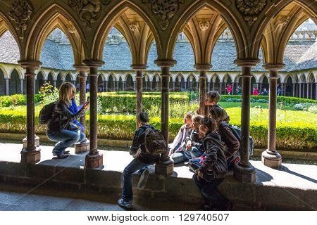Mont St. Michel France - May 22 2012: Normandy tourists taking pictures in the cloister of the abbey.