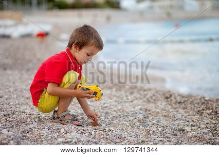 Boy, Playing On The Beach In The Evening After Rain With Toys