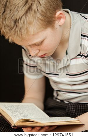 Single Boy Sitting And Reading A Book