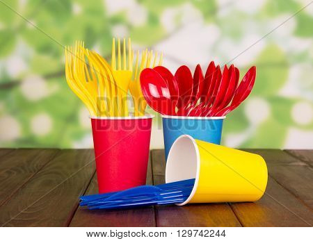 Multi-colored disposable plastic cups, forks, spoons on green abstract background