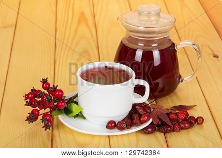 Jug and cup of rosehip drink on light wood background