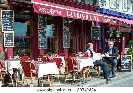 Honfleur France - May 19 2012: Normandy local people in a bar creperie in the old harbor basin