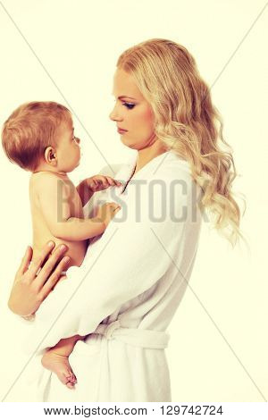 Young smiling mother in bathrobe holds her baby