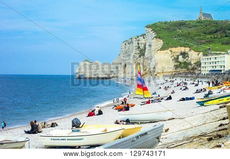 Etretat France - May 19 2012: Normandy local people relaxing on the beach near the cliffs .