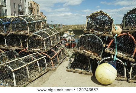 an image of lobster and crab pots stacked with fishing boats in the background