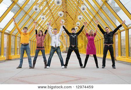 Grupo de amigos que estão tendo as mãos e subindo-os na passarela